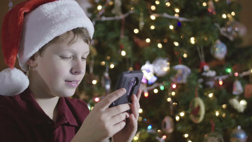 Young Boy Wearing Santa Hat Playing Game App on Cell Phone by Christmas Tree d9887dfe3e18