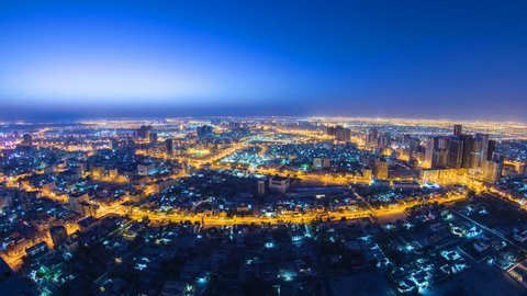 Cityscape of Ajman from rooftop from night to day transition timelapse. Ajman is the capital of the emirate of Ajman in the United Arab Emirates. fisheye 4K