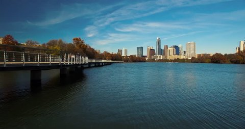 The camera hovers low over the water as it moves parallel to the boardwalk featured in Austin, Texas.  The city skyline is featured in the background as the camera gains altitude over Lady Bird Lake.