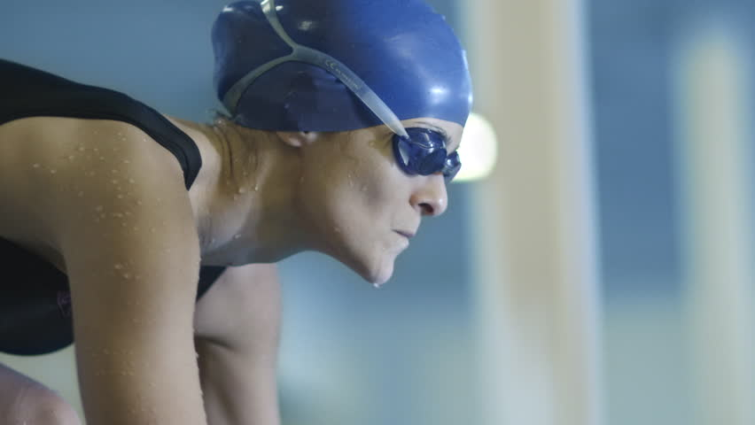 Professional Concentrated Female Swimmer in Goggles on Starting Block Before Jump into Water. Shot on RED Cinema Camera in 4K (UHD).