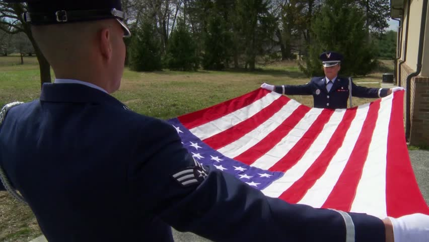 CIRCA 2010s - Soldiers from an honor guard perform a flag folding ceremony.