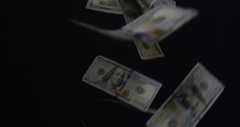 Hundred Dollar Bills raining down from the ceiling isolated on black in slow motion