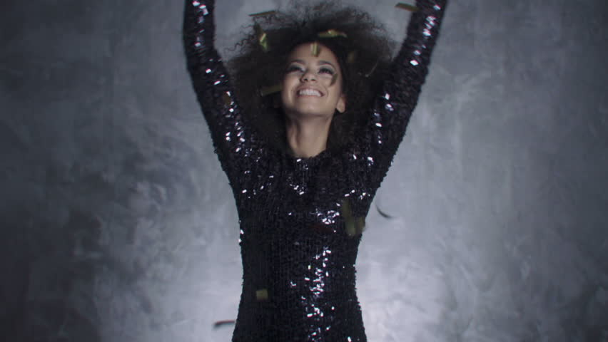 Beautiful black woman among golden confetti, slow motion. Sexy afro american woman dancing among confetti over silver background.