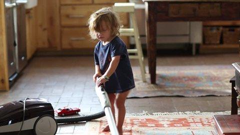 Toddler boy vacuuming at home