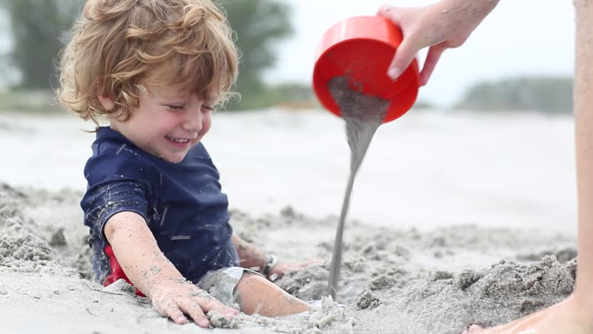 2 year old toddler boy playing with sand at the beach