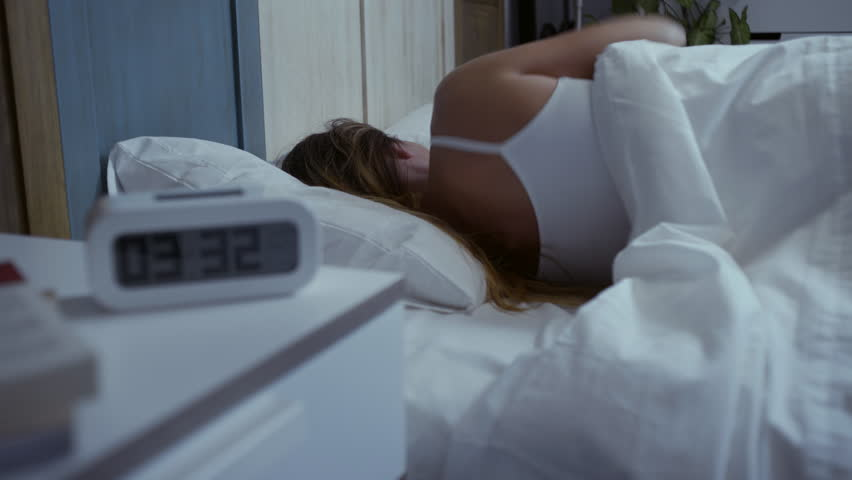 Young beautiful woman with insomnia can't sleep at night. The clock shows the hour: It's very late. Dolly shot.