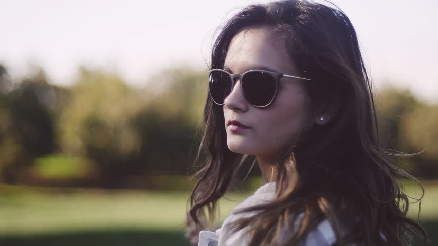 1663cb385825 Beautiful girl wearing sunglasses in a field, close up, slow motion. U. By  Uberstock. Stock footage ID: 13598351. Video ...