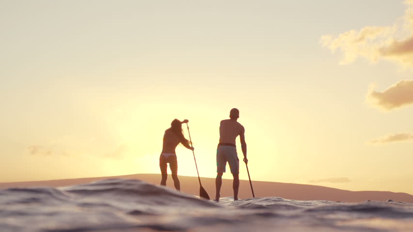 Slow Motion Couple Stand Up Paddle Boarding At Sunset