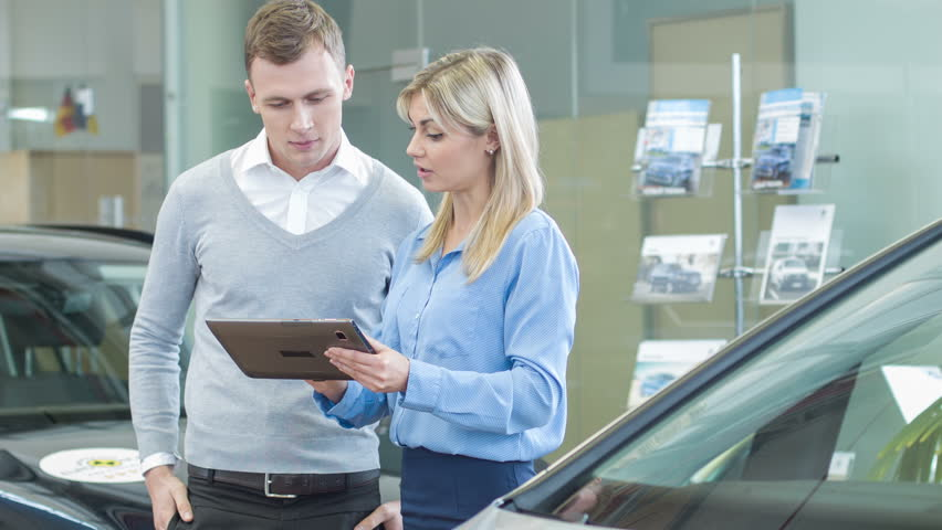 Digital variety. Young female salesperson is talking to her customer while showing various car models at the same time.