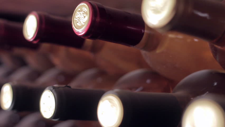 Dolly shot of wine bottles in an old wine cellar.