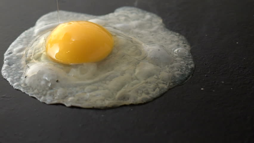 A slow motion video of a egg being dropped in mid-air and frying on a hot cast iron grill or skillet.  | Shutterstock HD Video #13702328