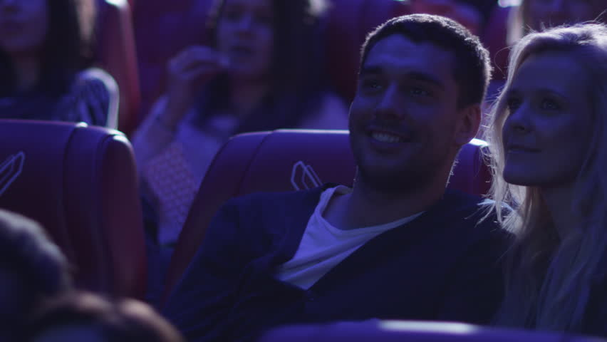 Young romantic couple is making out and kissing while watching a film screening in a movie cinema theater. Shot on RED Cinema Camera in 4K (UHD).
