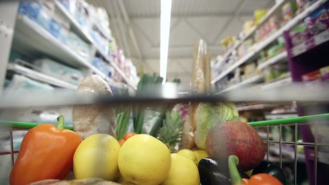 Full shopping cart with healthy food moving through aisles of supermarket. Time lapse