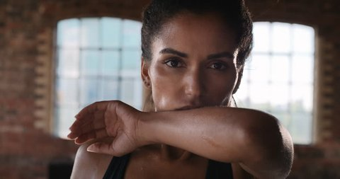 Beautiful Kickboxing woman tired from training with punching bag in fitness studio fierce strength fit body slow motion kickboxer