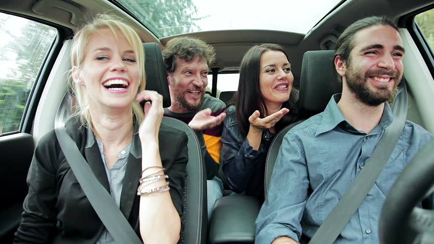 Two Women And Men In Car Talking With Friend On The Phone Laughing
