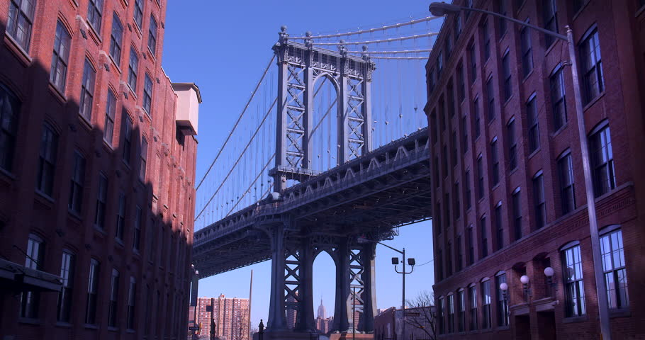 The Iconic Manhattan Bridge Viewed From Dumbo, Brooklyn. Zooming in from between two brick buildings with the Empire State building framed in the bottom of the bridge. (New York, August 2015)   Shutterstock HD Video #13782251