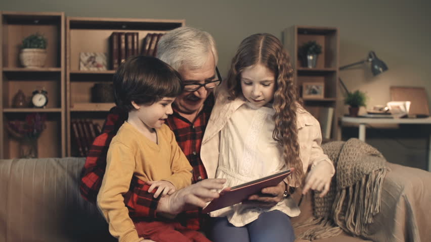 Grandfather entertaining his little grandchildren with a tablet computer game