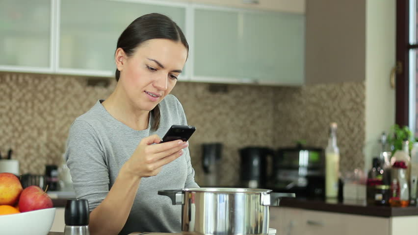 Brunette Woman In Kitchen Following Recipe On Mobile Phone Stock ...