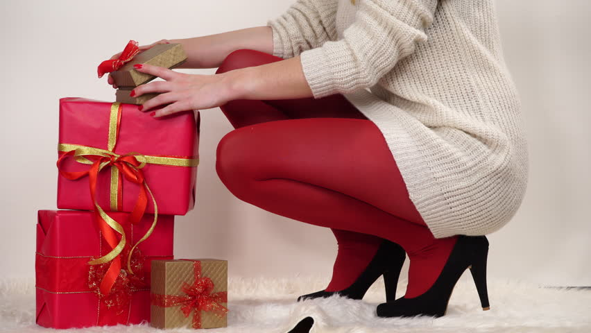 Woman in high heels opening christmas gift k stock