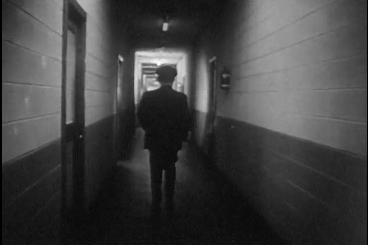 CIRCA 1950s - A security guard walks the hallway with his flashlight at a Zenith facility in the 1950s.   Shutterstock HD Video #13871411