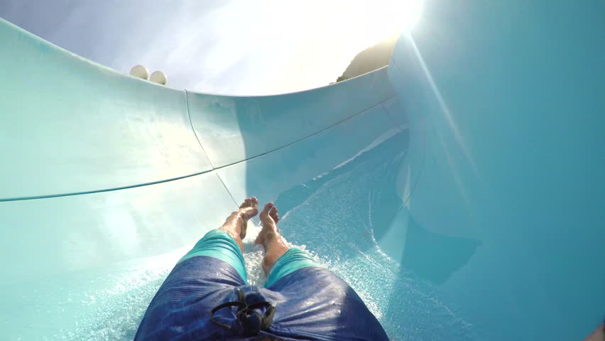 FPV FIRST PERSON VIEW POV: Young adult man sliding down the fun water slide at summer sunset | Shutterstock HD Video #13891583