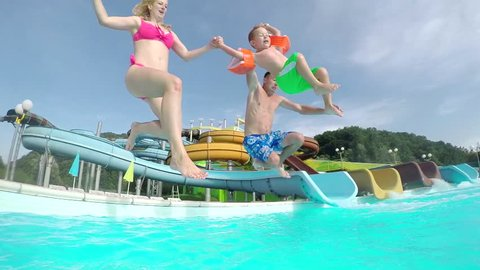 SLOW MOTION CLOSE UP: Happy excited young family running and jumping into the pool water in aqua park on a beautiful summer day on their holidays