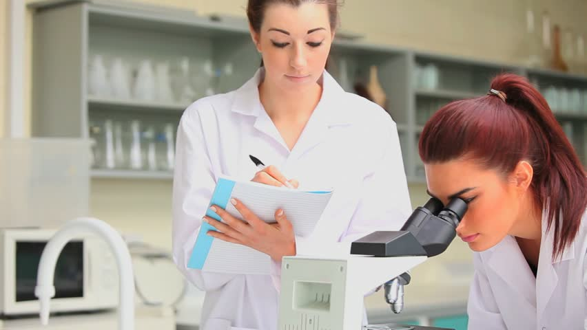 Science student looking in a microscope while her classmate is writing in a laboratory