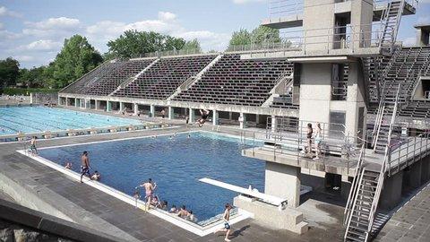 GERMANY - CIRCA JULY 2015 - Kids jump off diving board at Berlin Olympic Stadium pool, Germany
