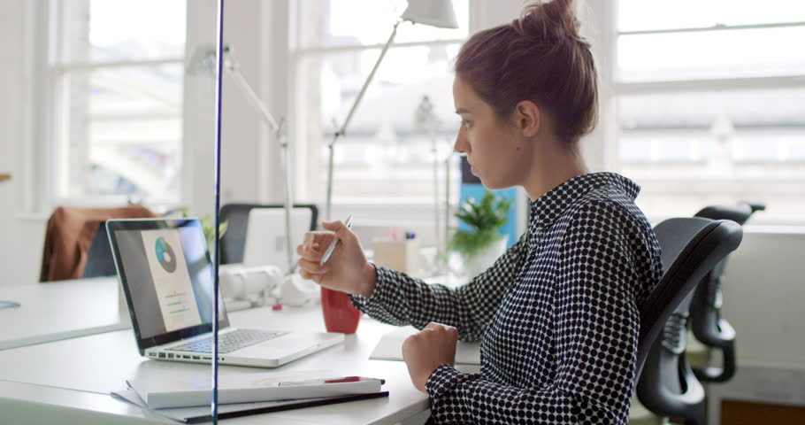 Young business woman working at shared desk in trendy hipster start up office using big data on laptop computer