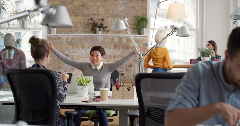 Business woman with arms raised celebrating success watching sport victory on laptop diverse people group clapping expressing excitement in office | Shutterstock HD Video #13949441