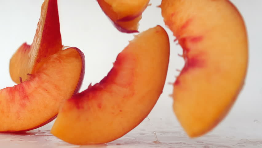 Peach slices falling on a wet surface