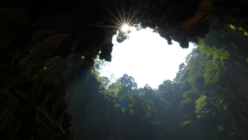 Impressive sunshine through open cave ceiling, blazing sunstar against black frame of cave vaults, green trees on gap edges, sun shine through foliage and leaves while camera panning move left.   Shutterstock HD Video #13981013