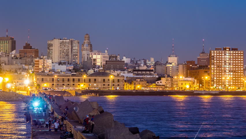 MONTEVIDEO - MAR 26, 2013: Timelpase view of Montevideo city with fishermen moving in the foreground ant the moon over the city on 26 March 2013 in Montevideo, Uruguay