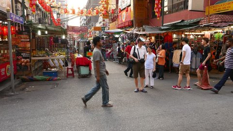 KUALA LUMPUR, MALAYSIA - FEBRUARY 28, 2015: POV rush through China town area market, stalls, crowd, restaurants. Colorful yellow and red-orange umbrellas hang above the street, chinese lifestyle