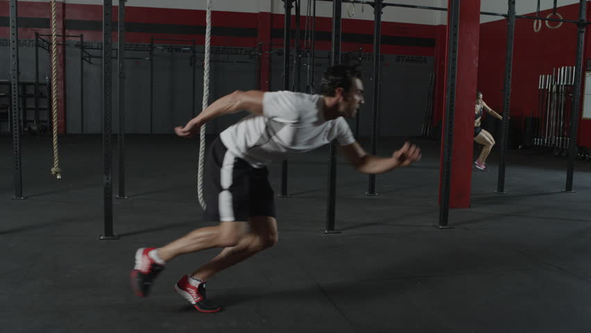 A man sprinting, touching the ground, and changing direction in a slow motion tracking shot - fitness / crossfit / exercise / workout / runner / running