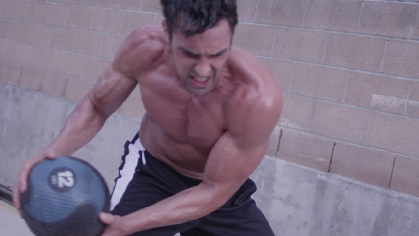 A strong, ripped, cut, buff man doing medicine ball exercises in slow motion, bouncing the ball off of a wall outside - fitness / crossfit / exercise / workout