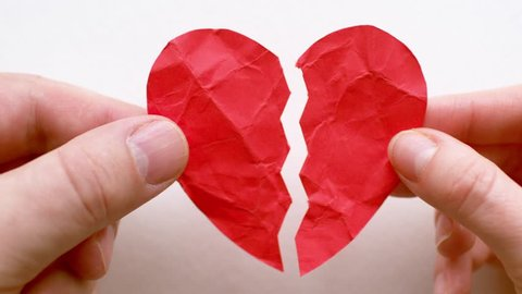 Female and male hands holding broken heart isolated on white