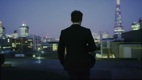 4k / Ultra HD version Successful businessman alone with his thoughts looks out over the view of the London city skyline at night. Shot on RED Epic