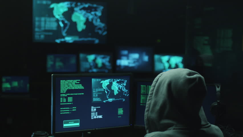 Male hacker in a hood works on a computer with maps and data on display screens in a dark office room. Shot on RED Cinema Camera in 4K (UHD). | Shutterstock HD Video #14018897