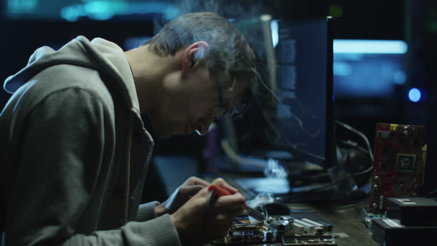 Electronics engineer is soldering an electric board with processors in a dark office with display screens. Shot on RED Cinema Camera in 4K (UHD).