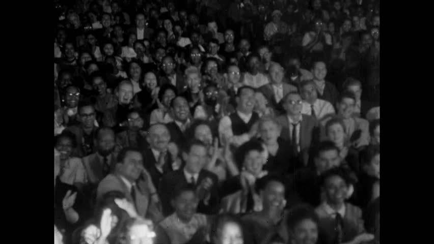 Audience applauding in theater as spotlight pans from left to right , 1950s
