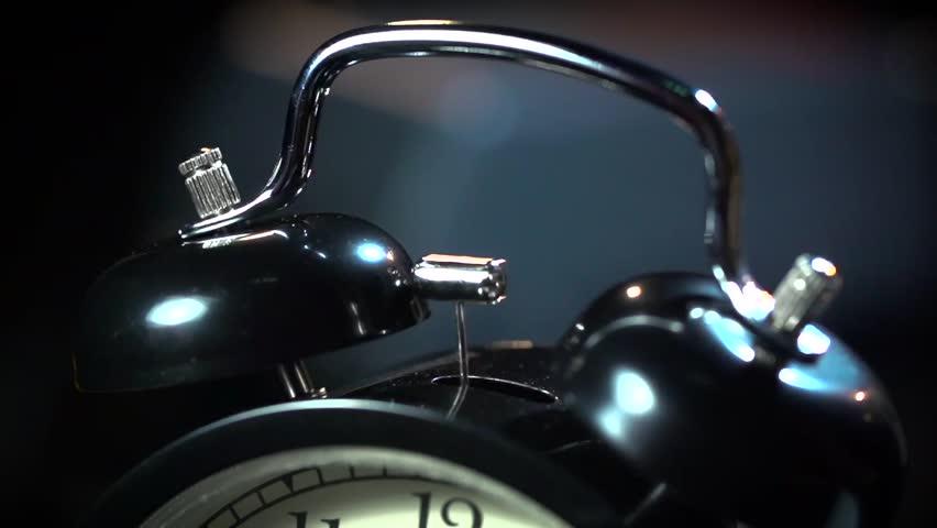 Super slow motion ancient desktop alarm clock on a black background macro