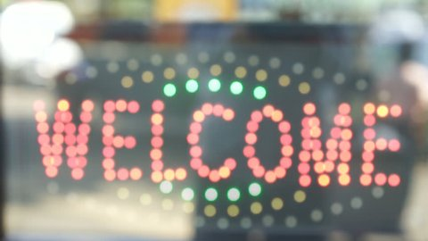 Welcome' led flash light sign on a storefront window