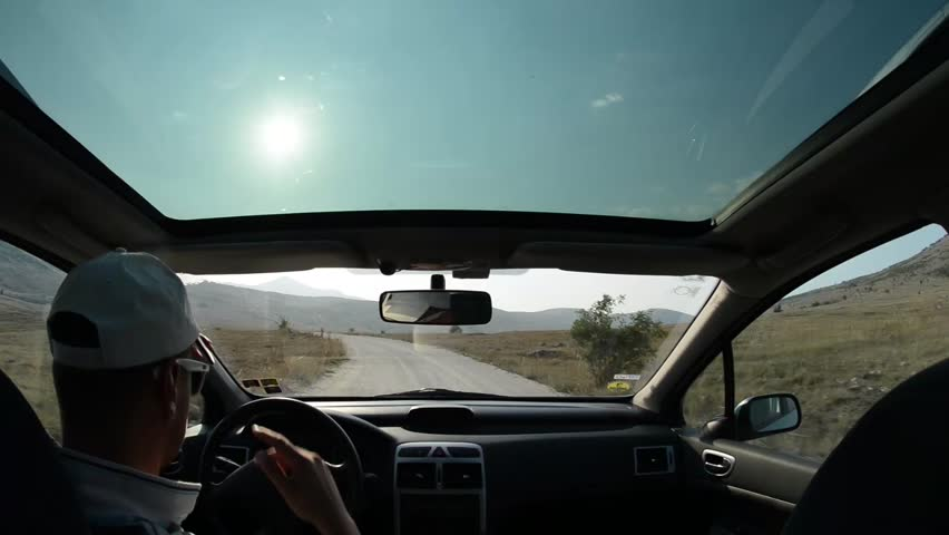 Man driving a car on country road trip in nature with sunset and sun flare, navigating with  smart phone navigation application | Shutterstock HD Video #14049011