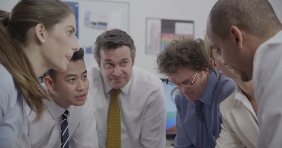 4k / Ultra HD version A diverse group of professionals are brainstorming in a business meeting in a room with lots of computer screens. They are seated around a glass table as they discuss ideas.  | Shutterstock HD Video #14050451