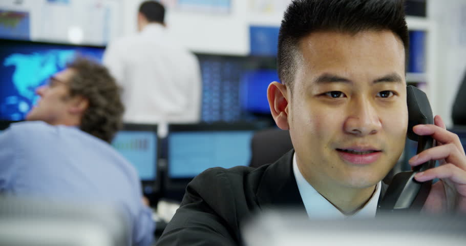 4k / Ultra HD version Portrait of a young and ambitious stock market trader working in a busy office filled with computers. The rest of his team are hard at work in the background. Shot on RED Epic | Shutterstock HD Video #14053691