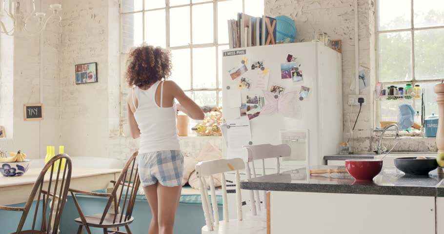 Happy curly haired girl dancing in kitchen wildly hair bouncing wearing pajamas at home having wild fun listening to music  | Shutterstock HD Video #14075624