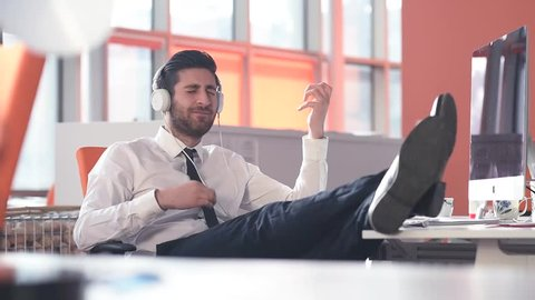 happy young startup business man listening music on phones and hold legs on table while playing guitar with hands