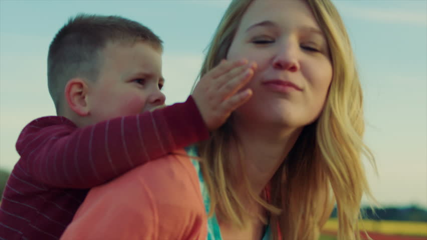 Young Teen Girl Gives Little Boy A Piggyback Ride In A Field Of Flowers In Bloom