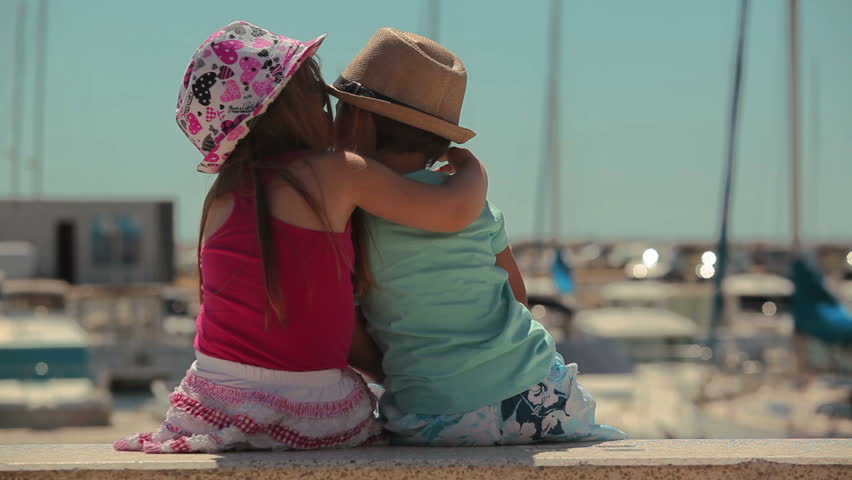 Girl kissing a boy. Little boy and girl sitting on a pier Yacht Club
